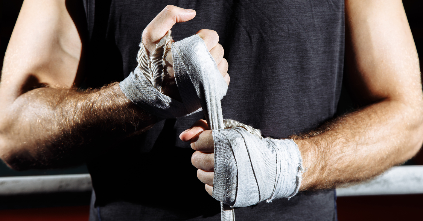 Strong man wrap hands on black background. Man is wrapping hands with boxing wraps, ready for training and active exercise.