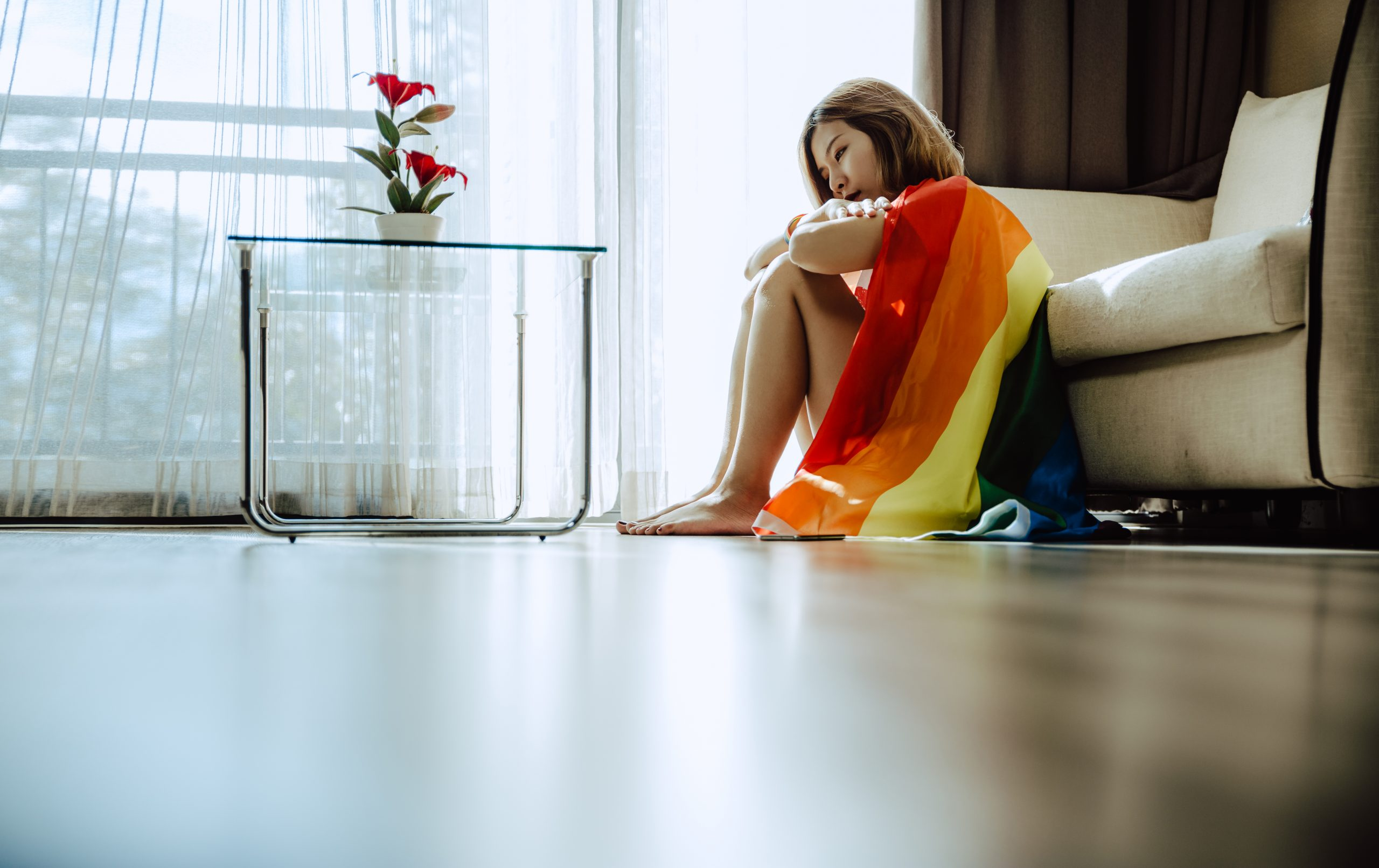 Young Asian girl covering with LGBT flag and sitting on the floor in living room.