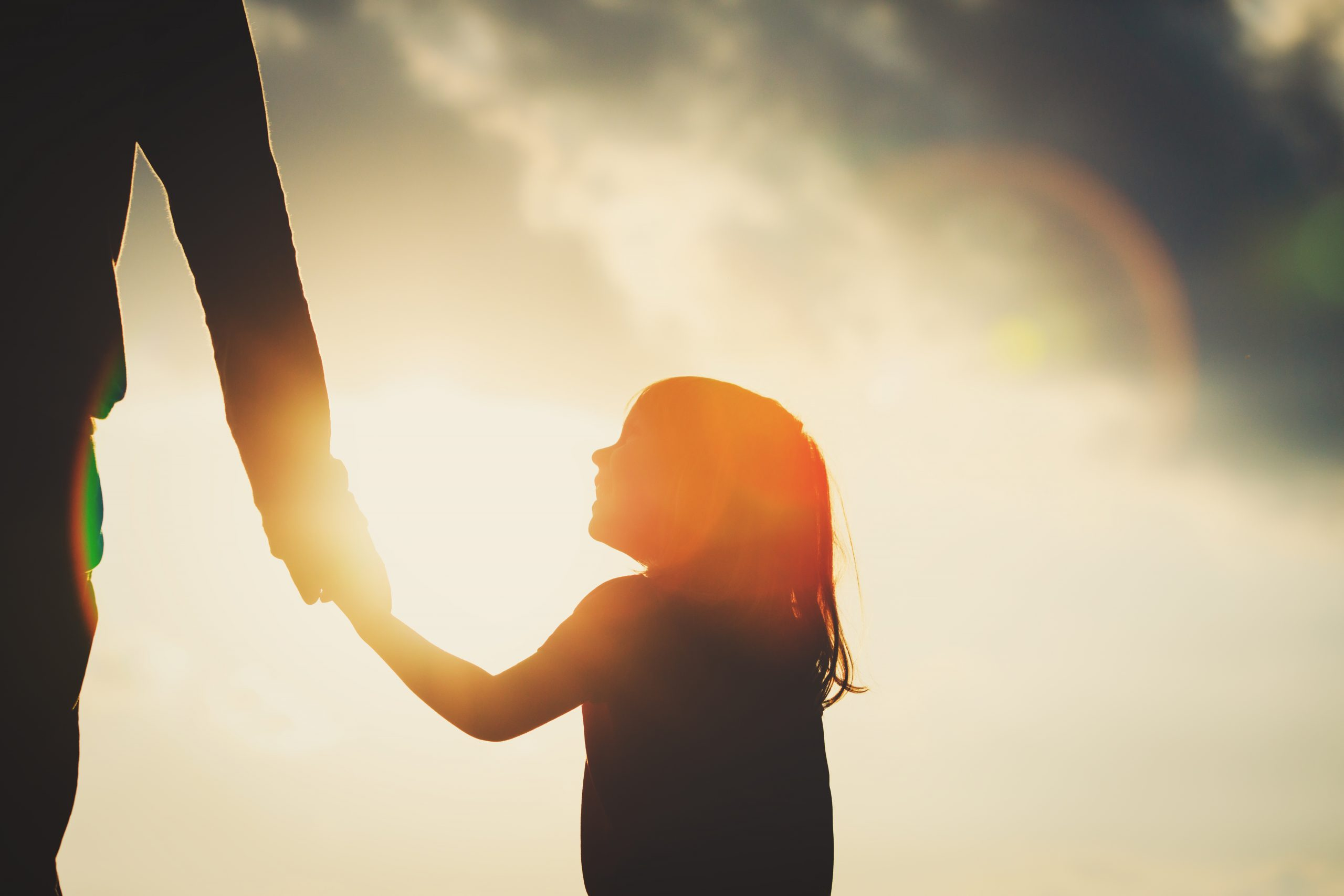 silhouette of little girl holding parent hand at sunset